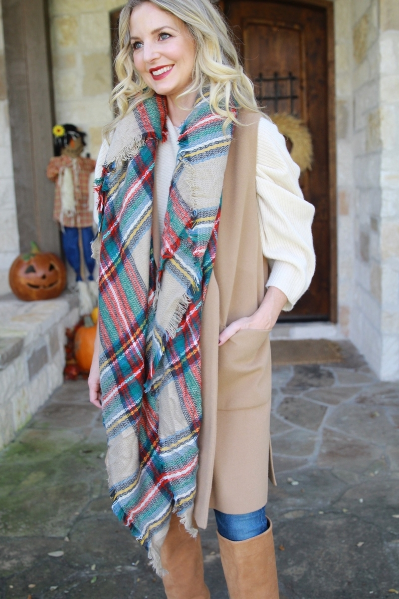 twisted red and green blanket scarf with camel vest and skinny jeans