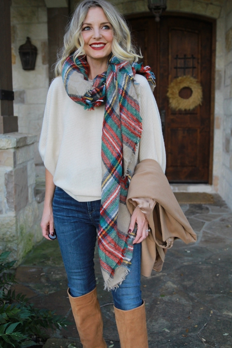 white cashmere sweater by marled by reunited from neiman marcus last call paired with a green and red blanket scarf slung over the shoulder, skinny jeans by ciitzens and tall suede camel boots