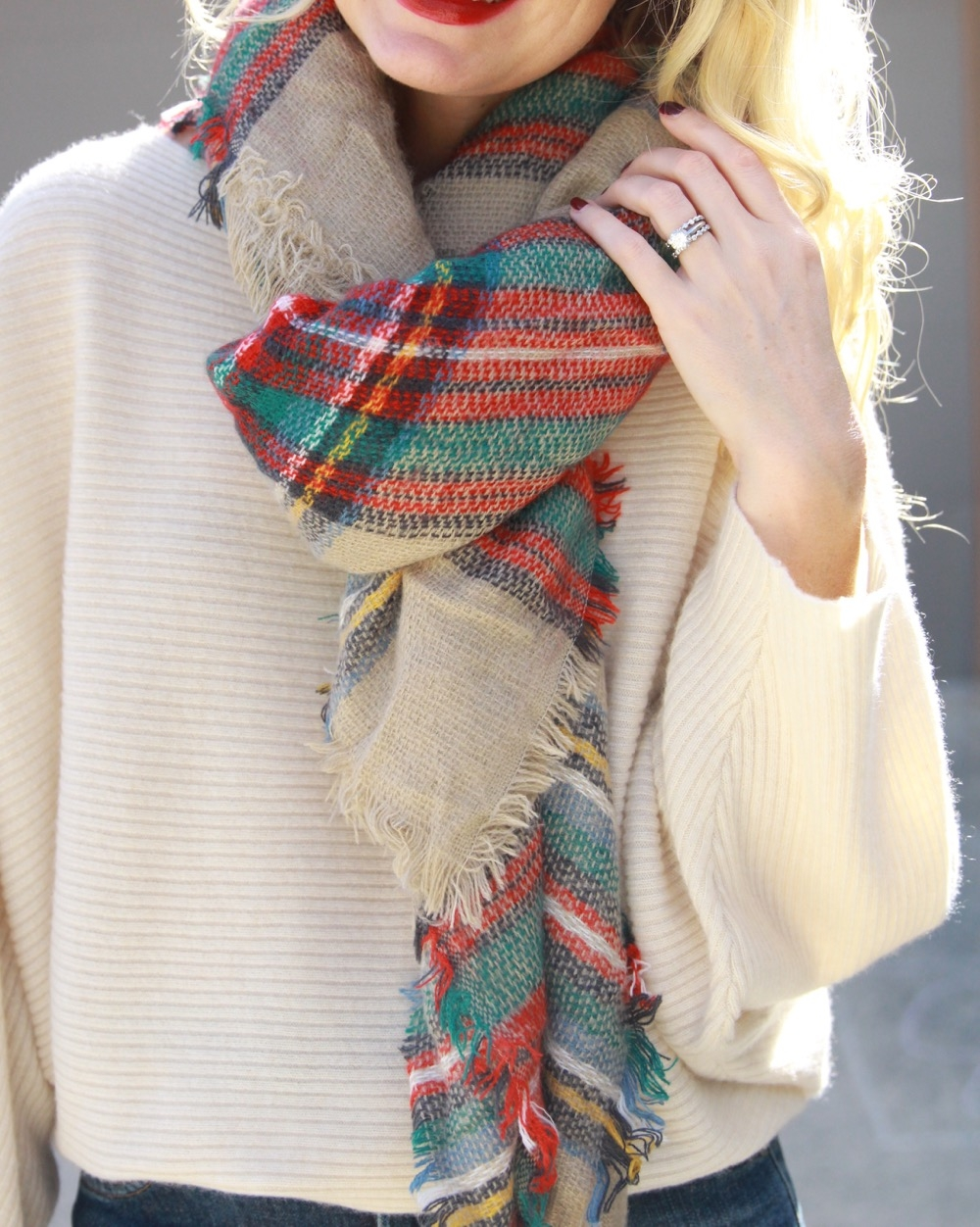 knotted blanket scarf in red and green with white cashmere sweater and red lipstick
