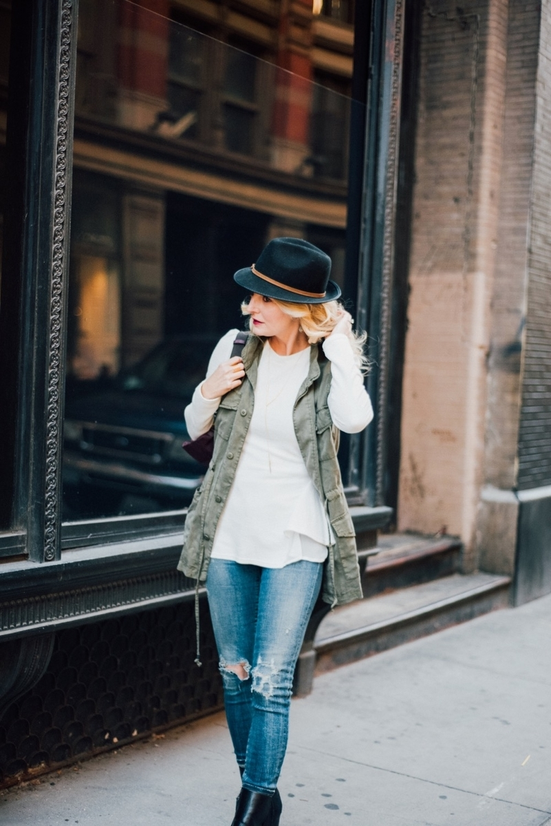 wearing a casual, street chic outfit in new york city, featuring a fedora, cargo vest from target, chicwish white peplum top and citiznens of humanity vintage skinny jeans