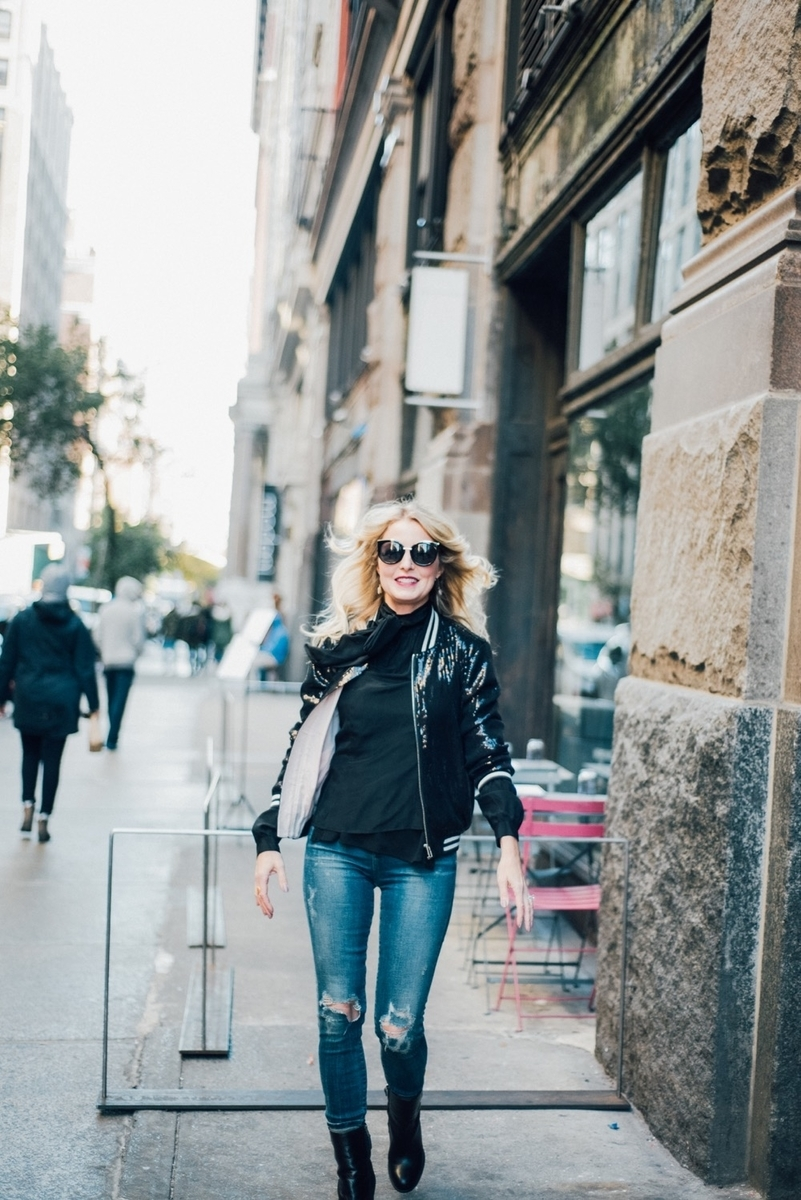 street style shot featuring an outfit idea for a bomber jacket, bb dakota sequin bomber jacket, with vintage, distressed skinny jeans by citizens of humanity and black sam edelman mid-calf booties