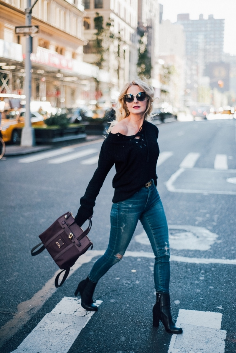 erin busbee from busbeestyle.com crossing nyc street in black laceup sweater with distressed skinny jeans by citizens of humanity rocket jeans, black booties, and henri bendel jetsetter backpack