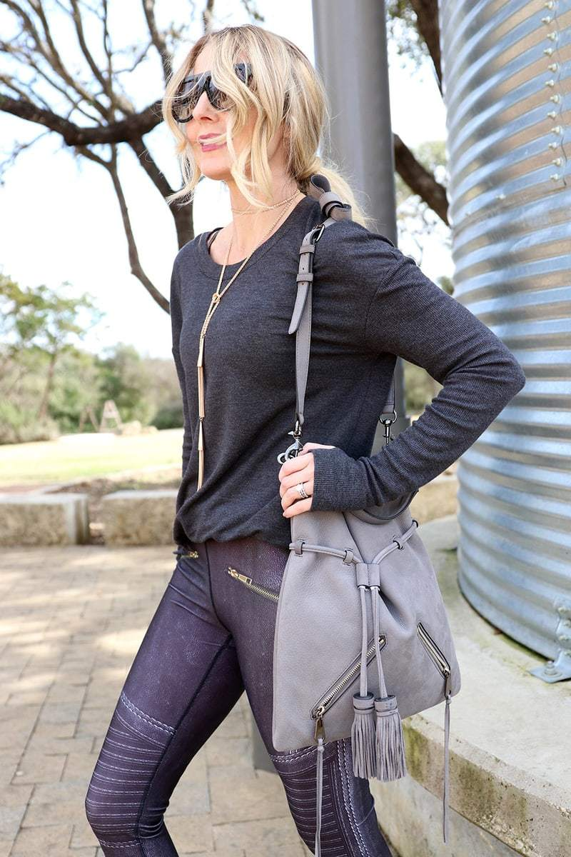one way to wear the athleisure trend, add a chic sweatshirt like this one from alo yoga, a piece of standout jewelry like this kendra scott gold tassel necklace and a great bag like this one by rebecca minkoff in gray suede with the tassel detailing, this gym to street look is from neiman marcus