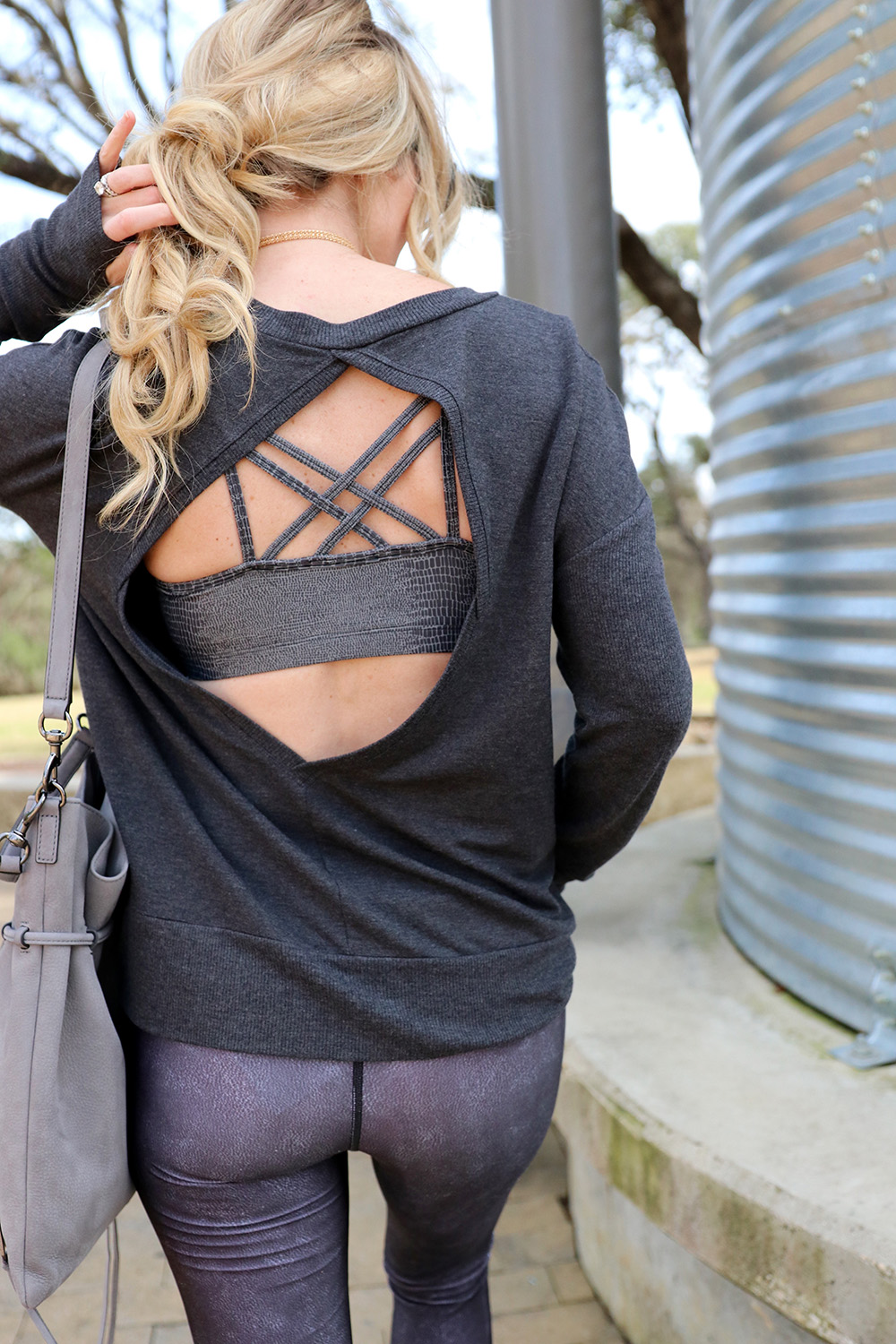 super sexy sports bra in silver with multiple straps peeps out from the alo yoga open back sweatshirt and running leggings with faux moto look