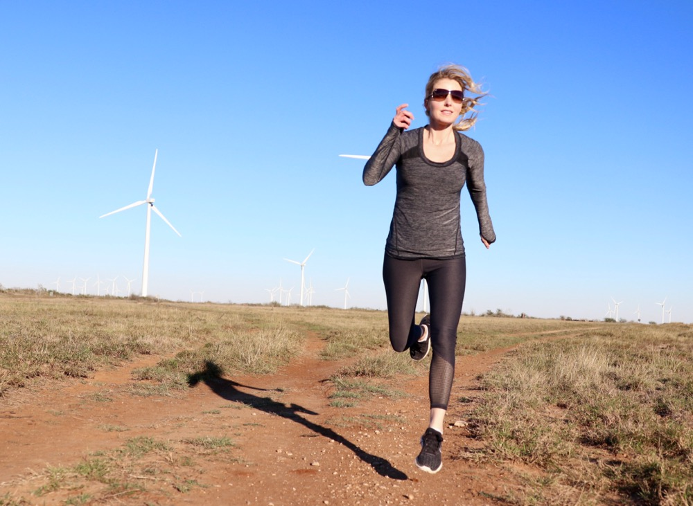 erin busbee, fitness, fashion, beauty blogger, running in the air, wearing zella exercise top and pants and under armour running sneakers
