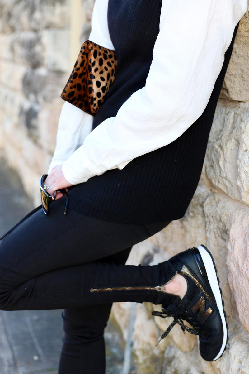 black and gold new balance sneakers add a sporty twist to a sweater and jeans. the claire v leopard clutch adds a pop of interest to the neutral color palette. This is one way to try the athleisure trend