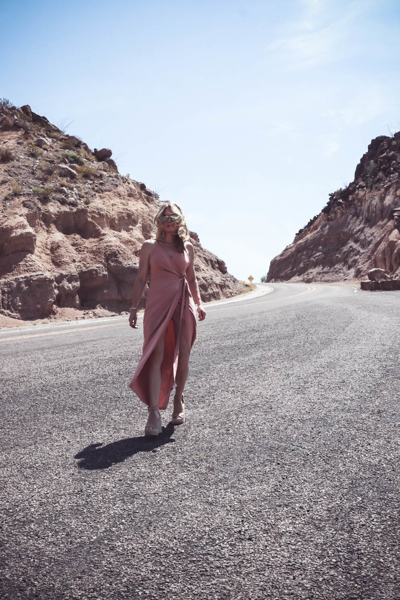 Wrap Dress by Wyldr from Asos and Revolve in blush nude color with Marc Fisher perforated ankle strap espadrilles wedges, on fashion blogger and fashion youtuber erin busbee of busbestyle, san antonio, texas, shot near Big Bend National Park in West Texas along the Rio Grande, walking on a rocky road in the desert