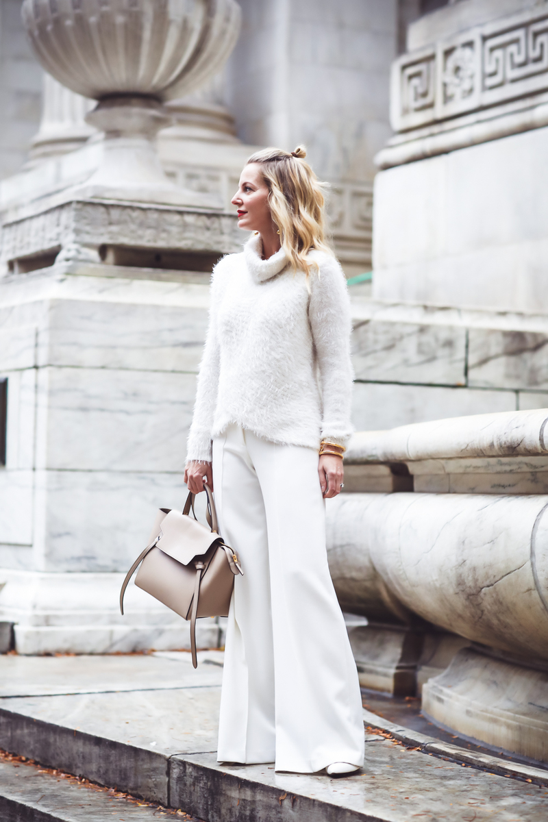 How to wear all white and still look slim, winter white, Fashion blogger Erin Busbee of Busbee Style in NYC wearing white wide leg trousers by Milly and a fuzzy white sweater with Celine belt bag and who what wear white target mules