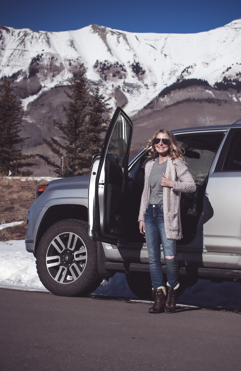 Fuzzy Cardigan sweater paired with Sorel Conquest boots, AMO twist jeans, on fashion blogger over 40, Erin Busbee of Busbee Style in Mountain Village, Telluride Colorado in front of Toyota 4-runner limited