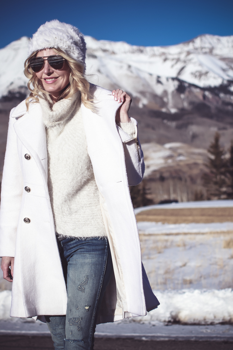 White coat, winter white coat, double breasted by Guess in boucle, paired with Sorel Conquest booties, Amo twist skinny jeans, a white fuzzy hat and a fuzzy white sweater, on Fashion Blogger over 40, Erin Busbee of Busbee Style, BusbeeStyle.com in telluride, Colorado in the snowy mountains
