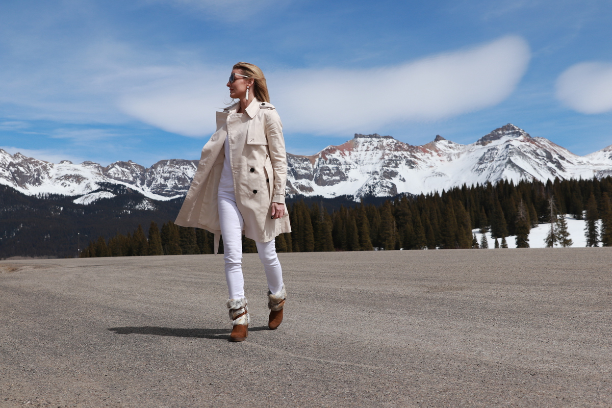 wearing Club Monaco champagne colored trench coat, white jeans, boots, corset sweater, Light Layers for Spring