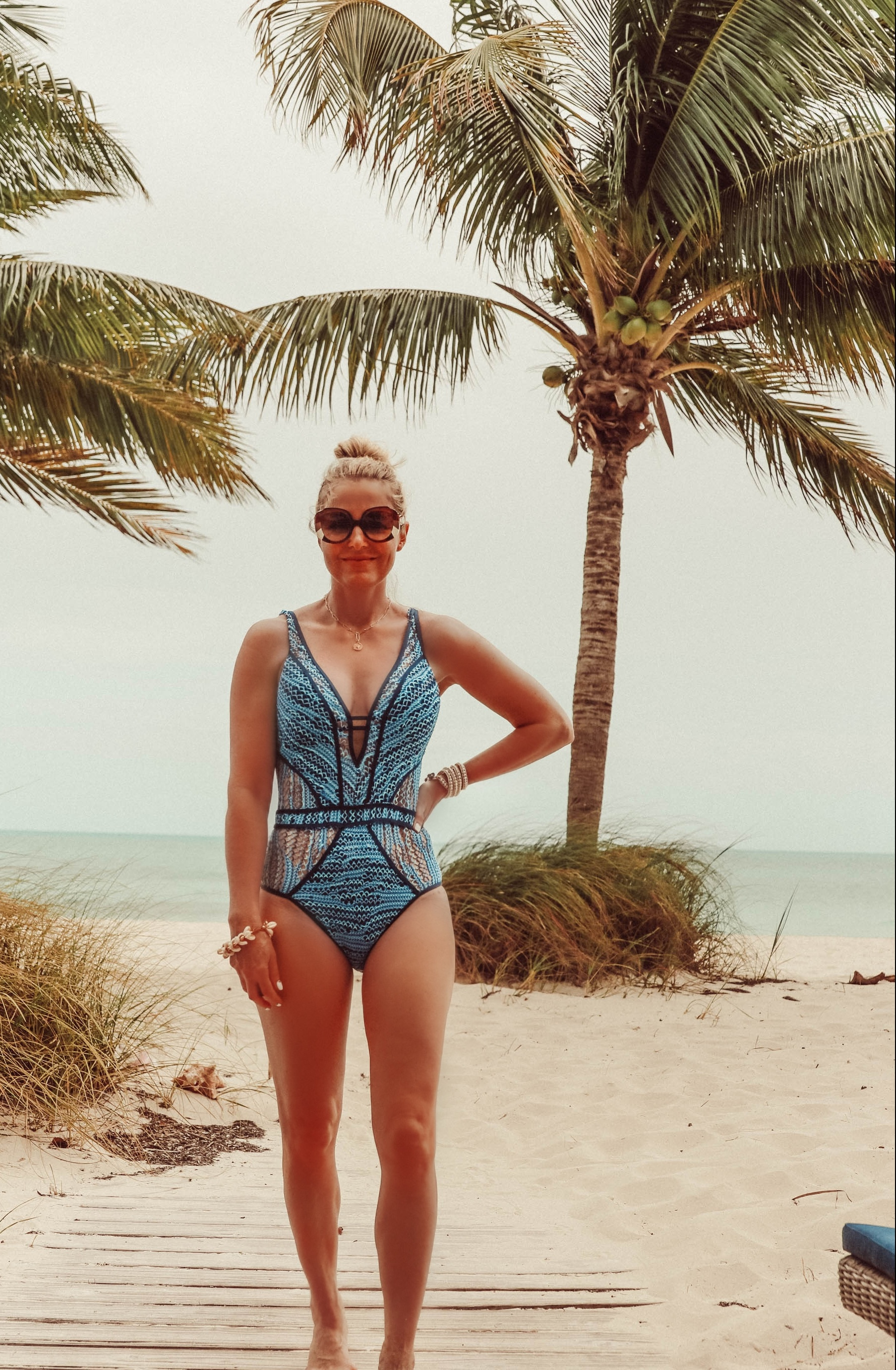 Flattering Swimsuits, Fashion blogger Erin Busbee of BusbeeStyle.com wearing a blue Becca one piece with plunge neckline in the Bahamas