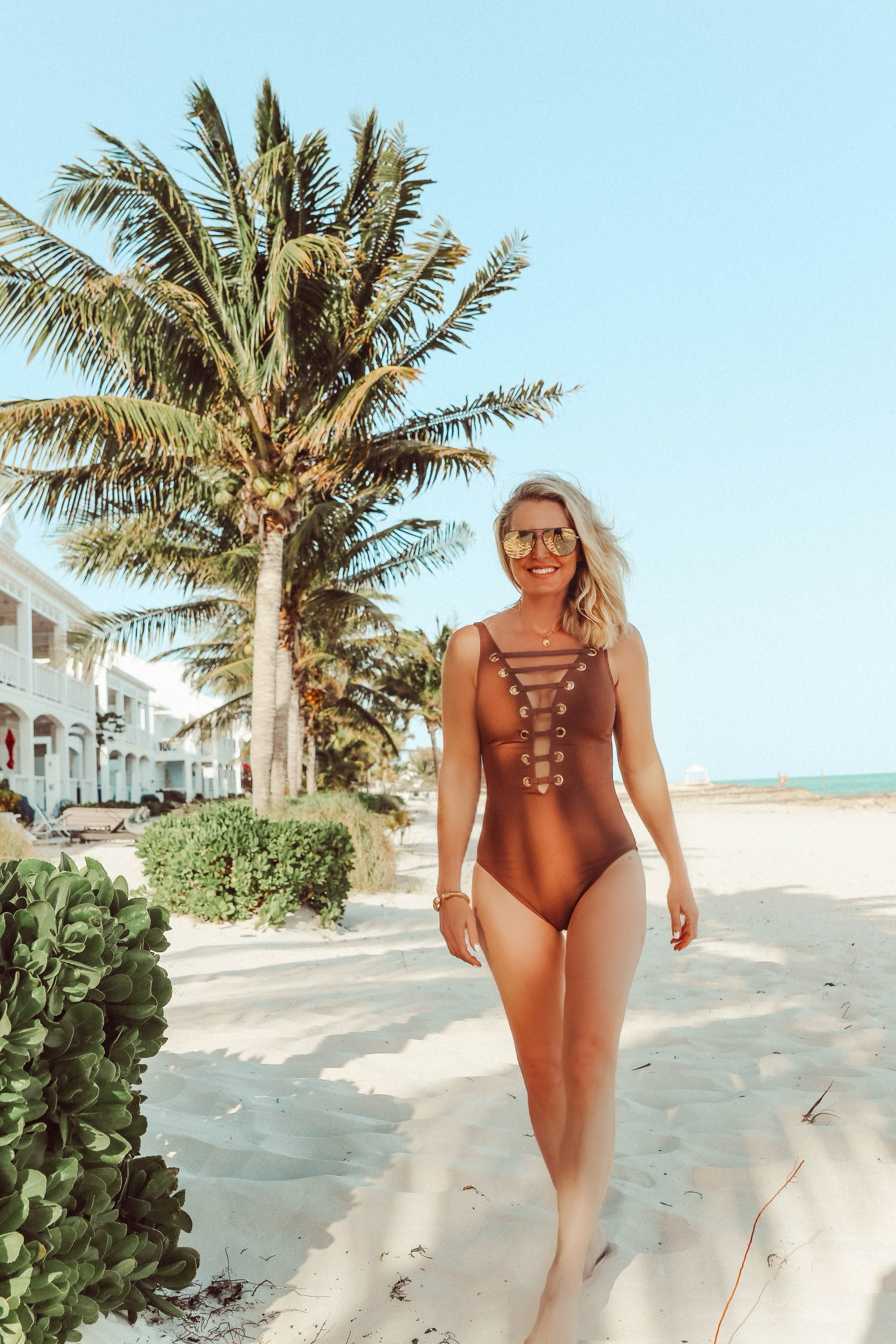 Flattering Swimsuits, Fashion blogger Erin Busbee of BusbeeStyle.com wearing a brown strappy one-piece swimsuit by Bleu Rod Beattie in the Bahamas