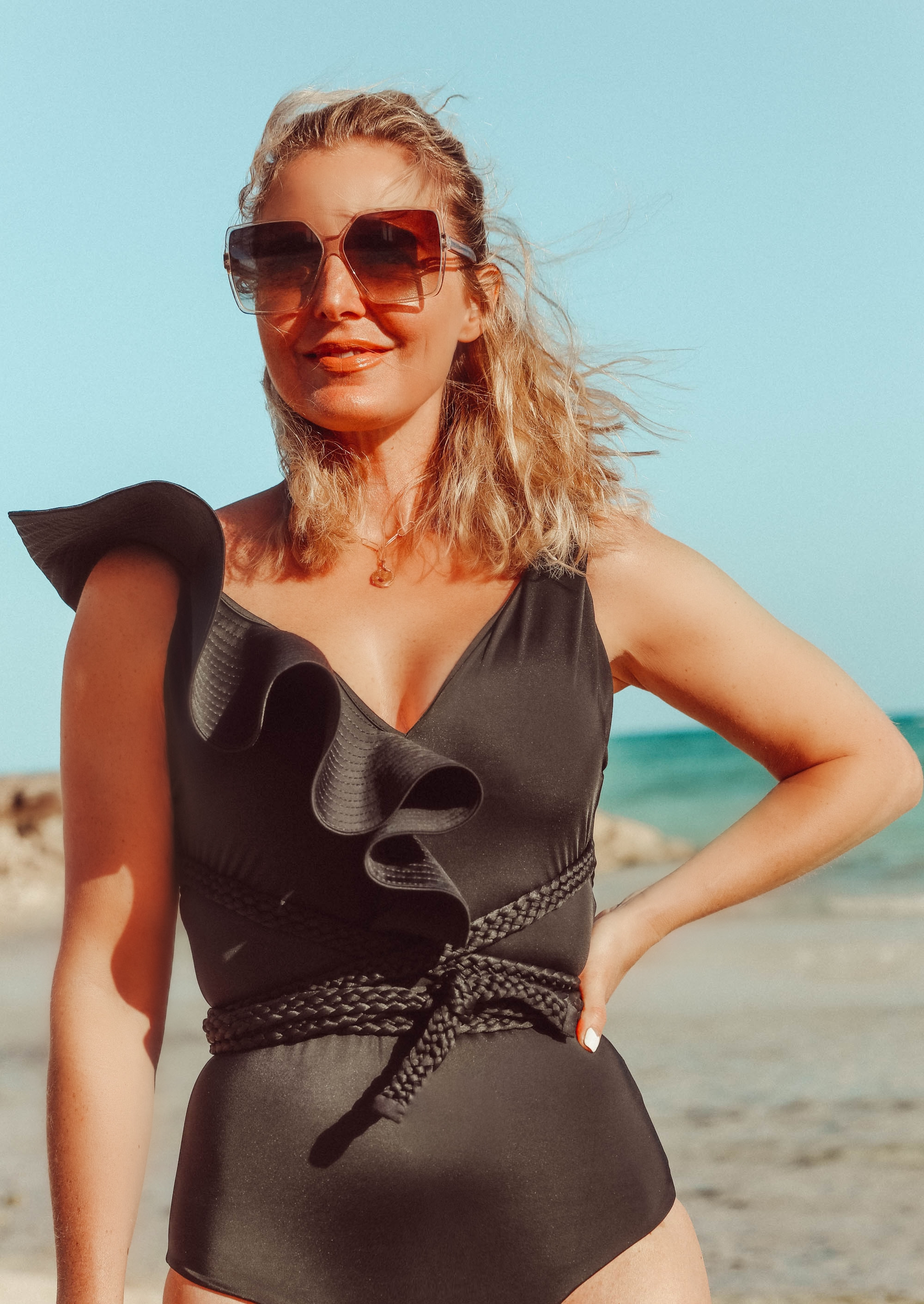 Flattering Swimsuits for women over 40, Fashion blogger Erin Busbee of BusbeeStyle.com wearing a ruffled one shoulder bikini by Johanna Ortiz with matching brown bikini bottoms in the Bahamas