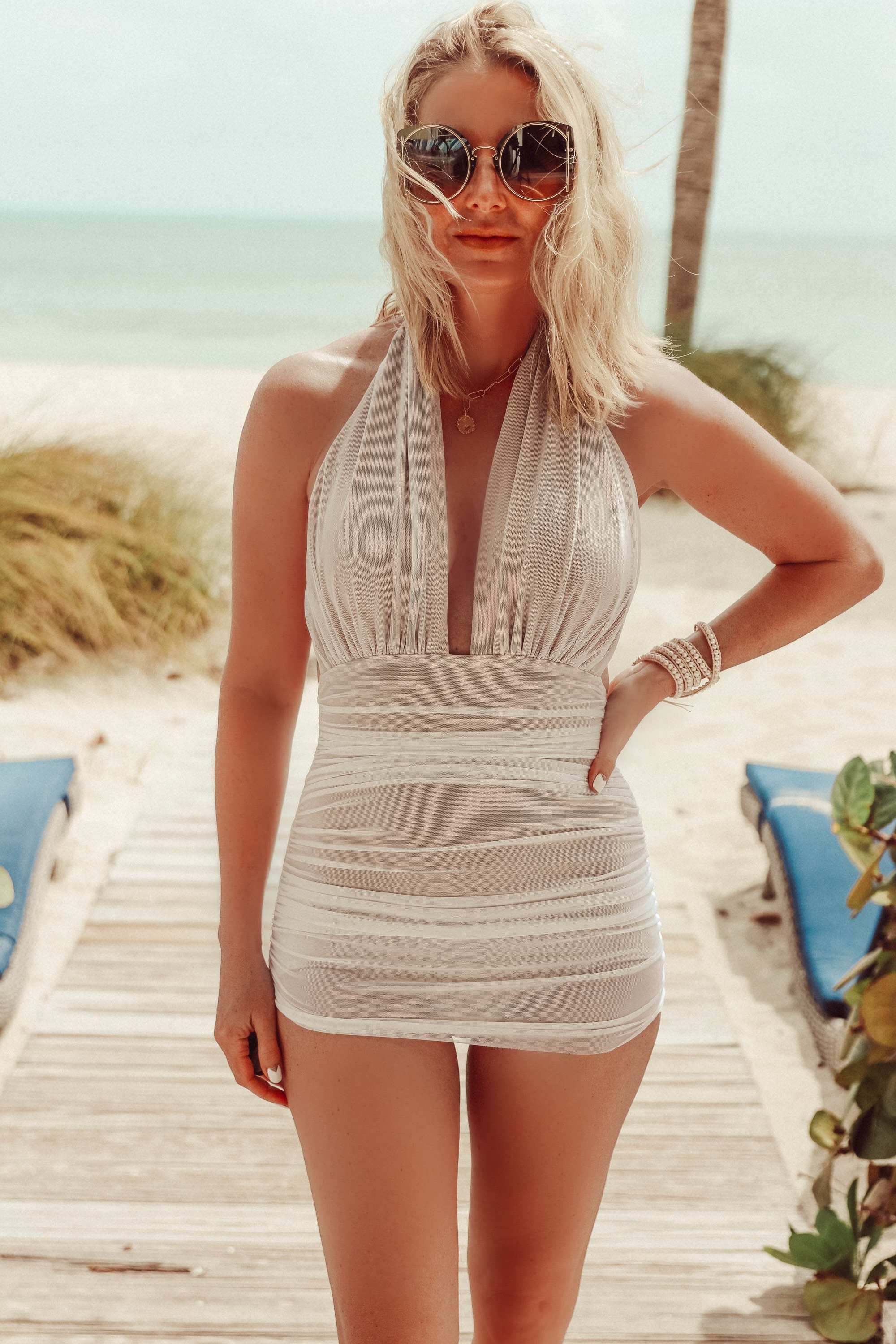 Flattering Swimsuits, Fashion blogger Erin Busbee of BusbeeStyle.com wearing a halter neck mesh overlay one-piece swimsuit by Norma Kamali in the Bahamas