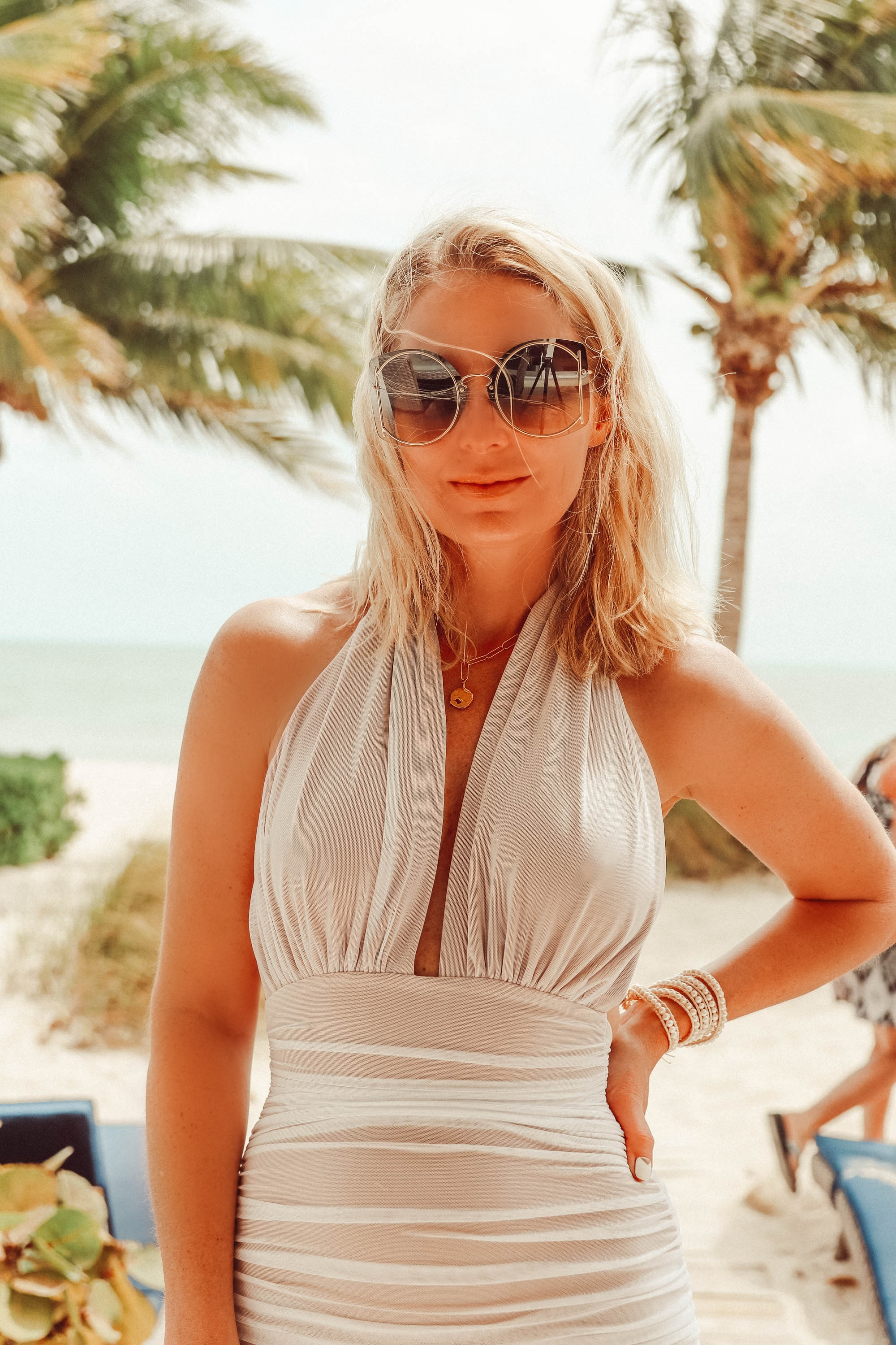 Fashion blogger wearing flattering Norma Kamali halter neck mesh overlay one-piece swimsuit and natural self-tanning product on beach