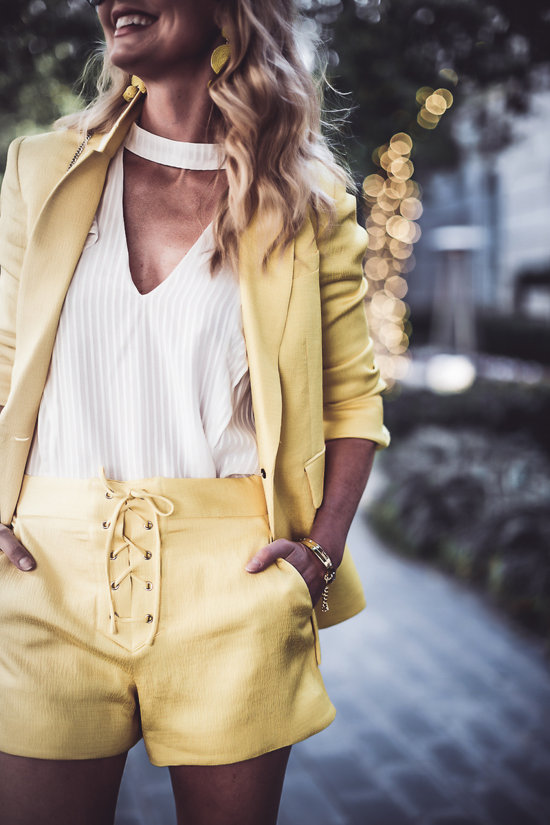 reward style blogger conference 2018, blonde fashion blogger walking in a yellow shorts suit by Veronica Beard at Hotel Crescent court carrying a Henri Bendel Rivington pouch in bright yellow