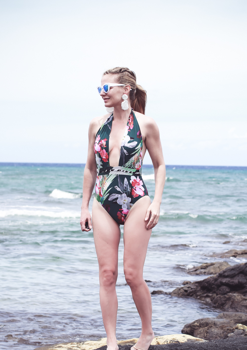 one-piece swimsuit in tropical print with plunging neckline by La Blanca, on a blonde woman standing on the lava rock in Hawaii