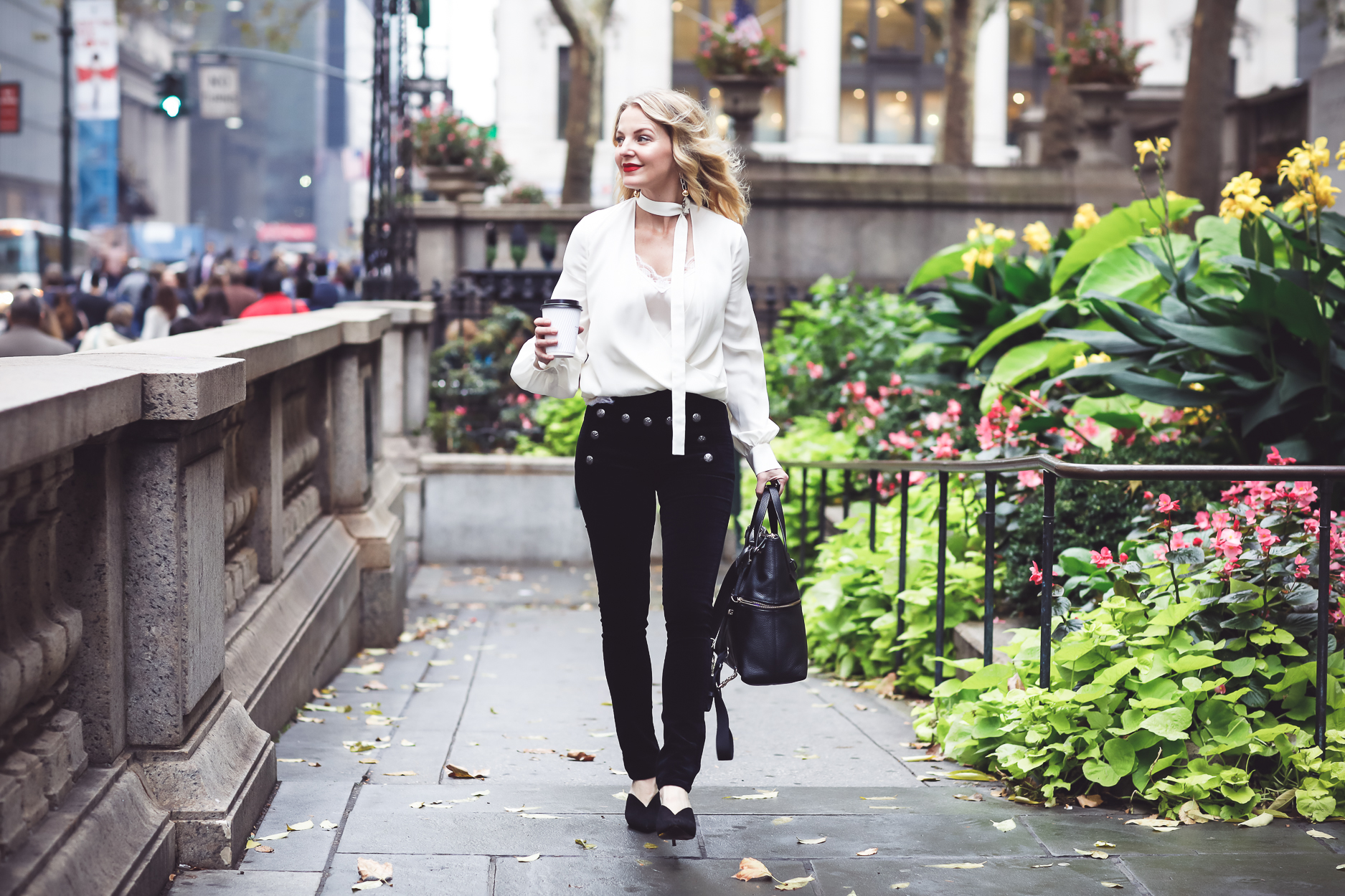 Blonde woman wearing white choker blouse by Alexis, Black velvet veronica beard skinny pants with sailor buttons and black mules by who what wear carrying a Henri Bendel bag in Bryant Park in NYC