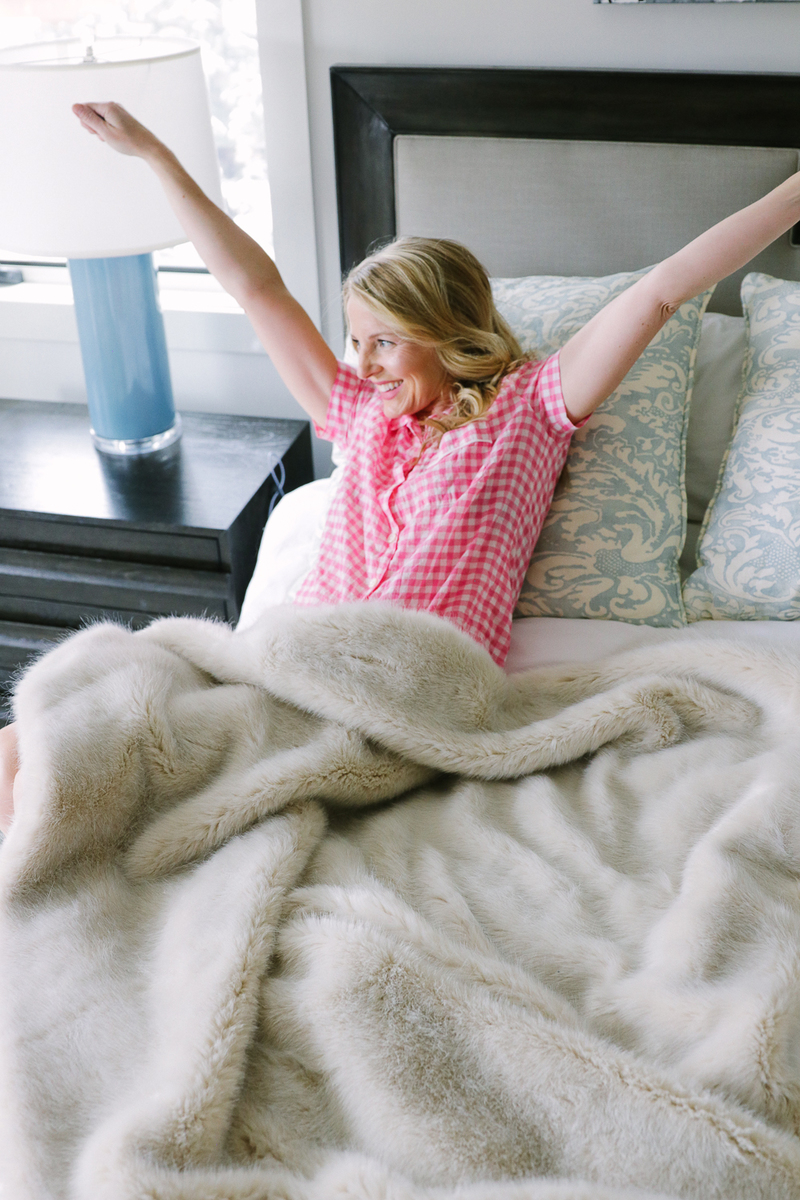 blond woman stretching in pink J.Crew gingham pajamas sitting in white king bed
