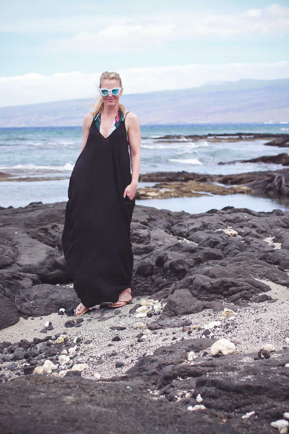 favorite beach or pool swim coverups on blonde woman featuring a black Elan maxi dress with pockets and La Blanca tropical jungle one piece swimsuit with white retro sunglasses