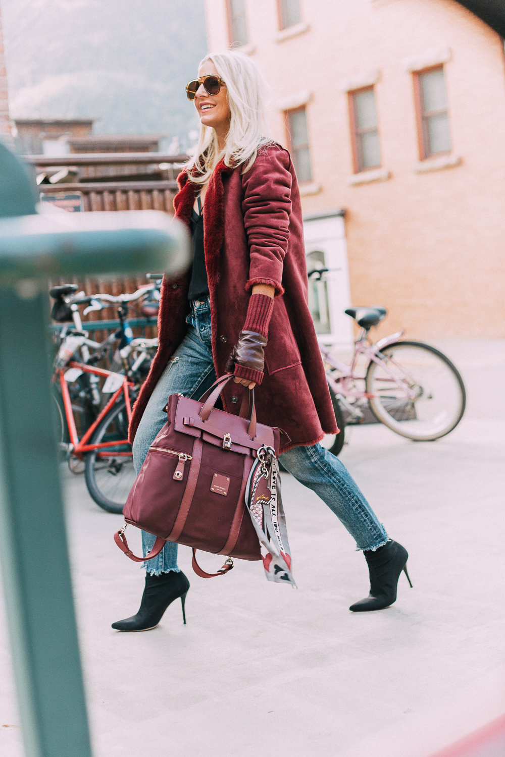 burgundy Jetsetter backpack paired with burgundy plush coat, cropped Moussy jeans, Stuart Weitzman sock booties and fingerless gloves