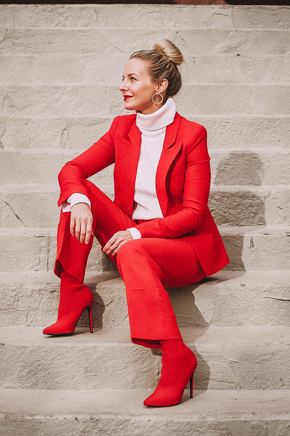 Red suit by Smythe, dutchess blazer and cropped pants with red Steve Madden sock booties on blonde woman