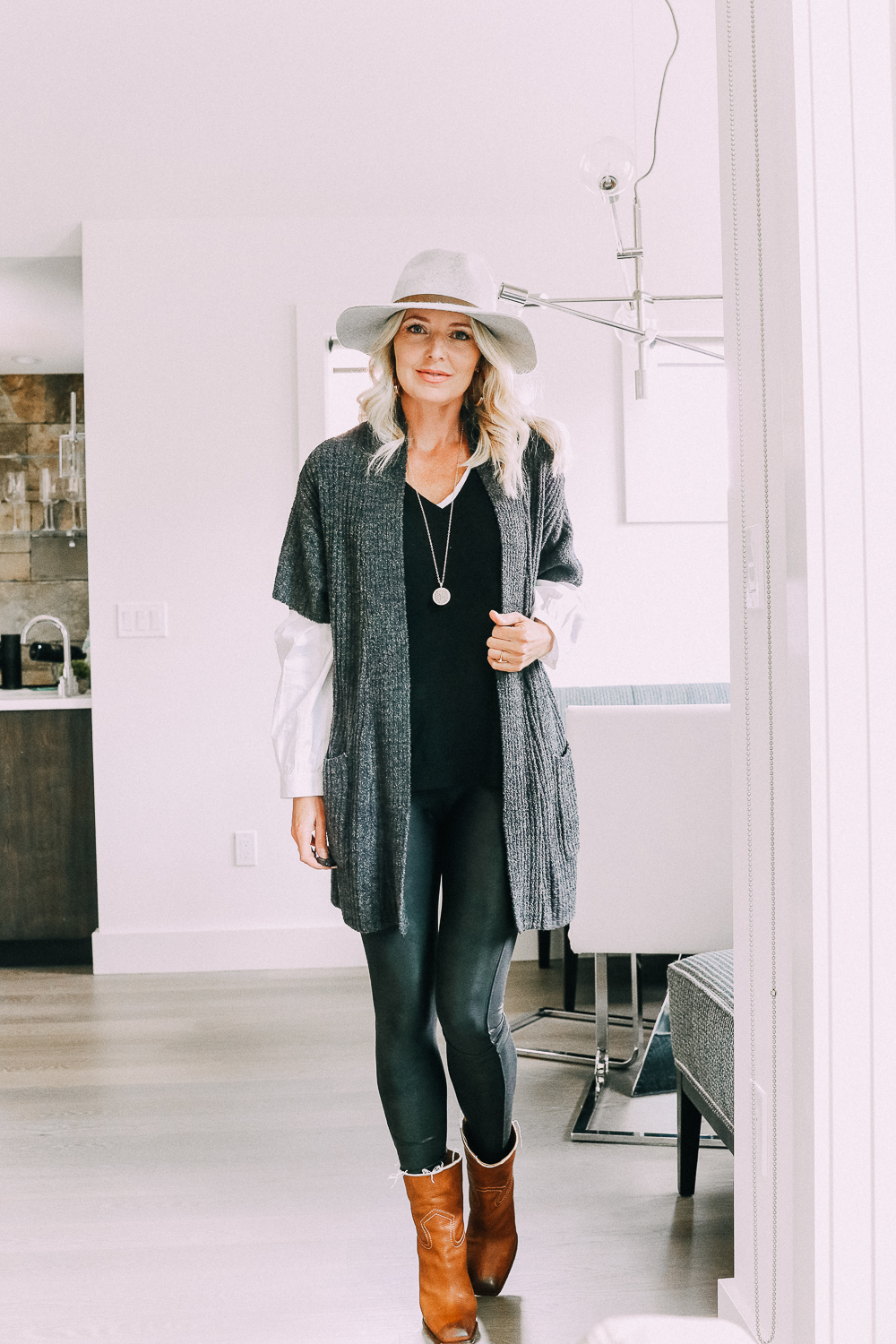 Blonde woman wearing jeans, layered sweater, Barefoot dreams cardigan, Saint Laurent boots, and a Rag & Bone hat in Telluride Colorado sharing chic and casual looks for busy moms