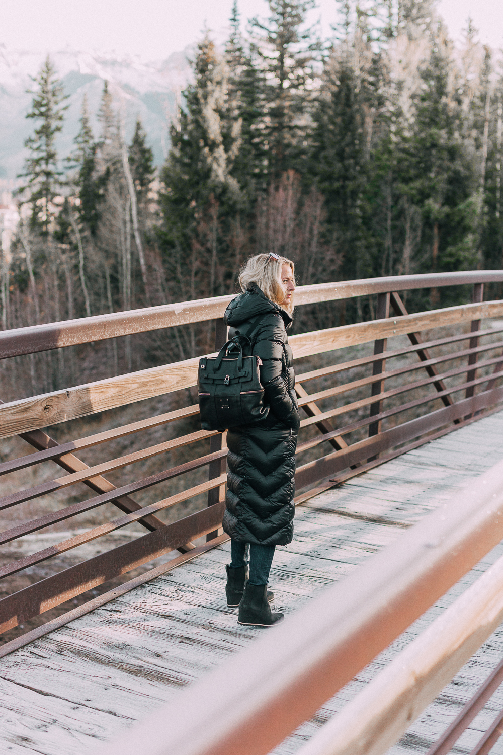 best puffer coats for women by Parajumpers from Bloomingdales in black, long puffer coat paired with dark jeans, black Ugg wedge booties on blonde woman