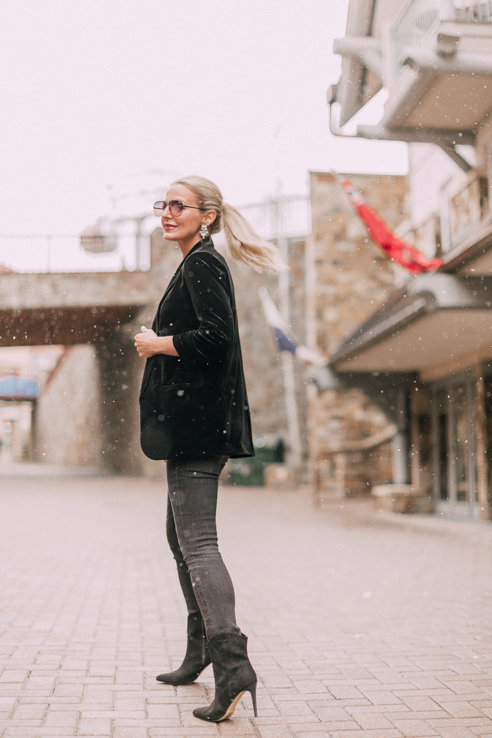 Unexpected holiday party outfits featuring gray jeans, sequin camisole, black velvet boyfriend blazer with ruched 3/4 sleeves on blonde fashion blogger in Telluride, Colorado wearing black western style ankle booties