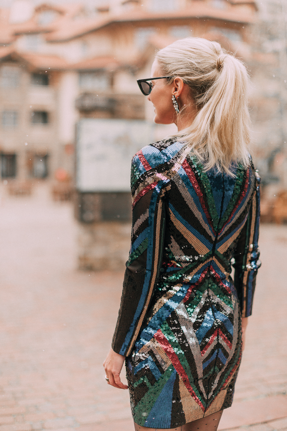Unexpected holiday party outfits featuring a long-sleeve, colorful sequin mini dress from Express on blonde fashion blogger in the snow in Telluride, Colorado