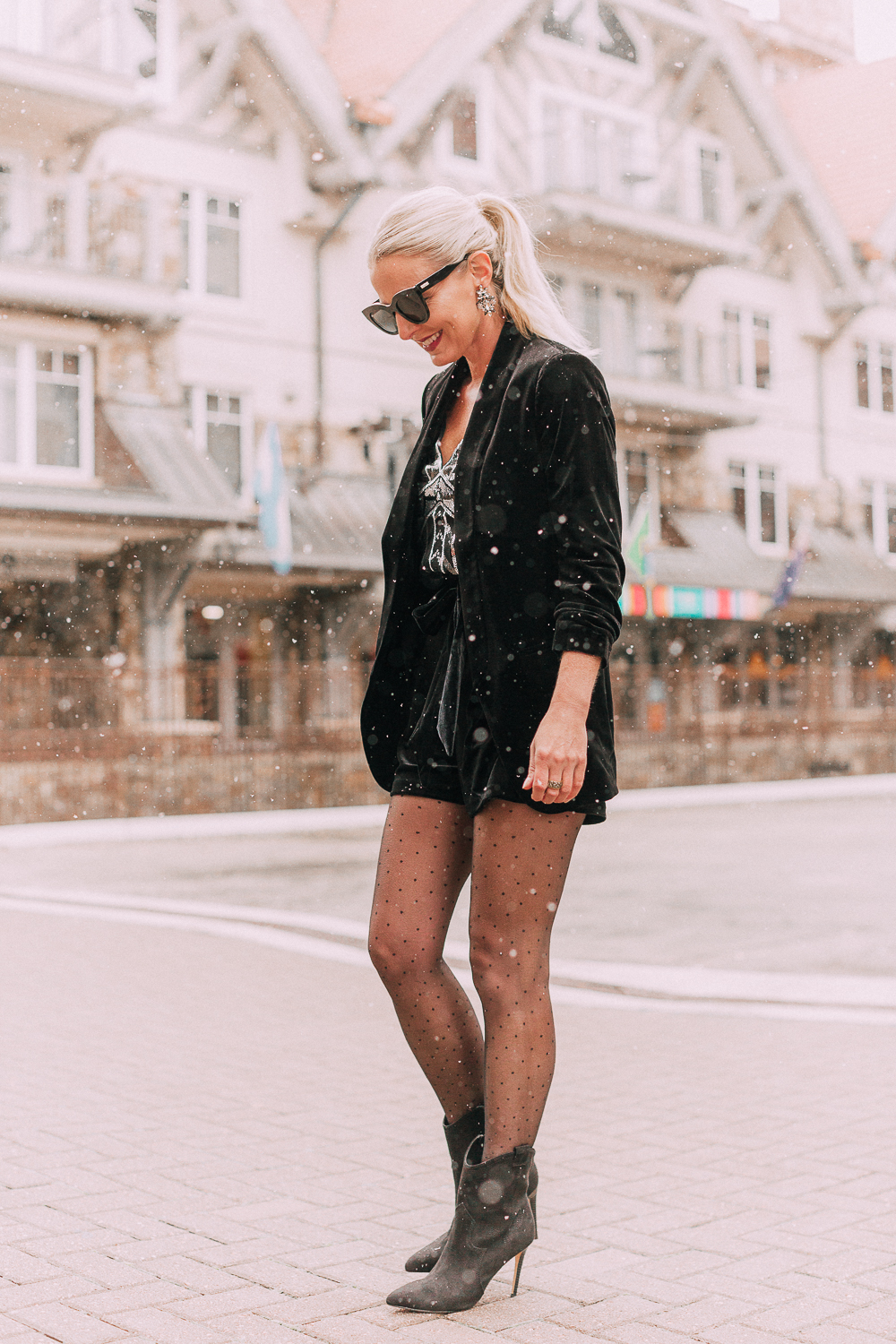 Unexpected holiday party outfits featuring a velvet Shorts suit from Express paired with Western black booties, and polka dot black tights on fashion blogger with blonde hair