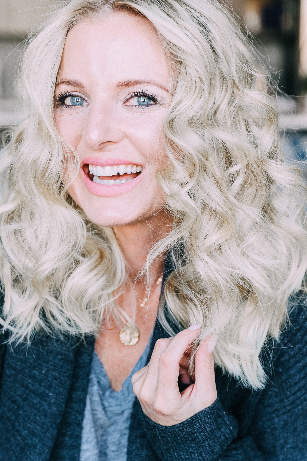 Curling your hair with a wand, step by step instructions by beauty blogger Erin Busbee with long blonde hair