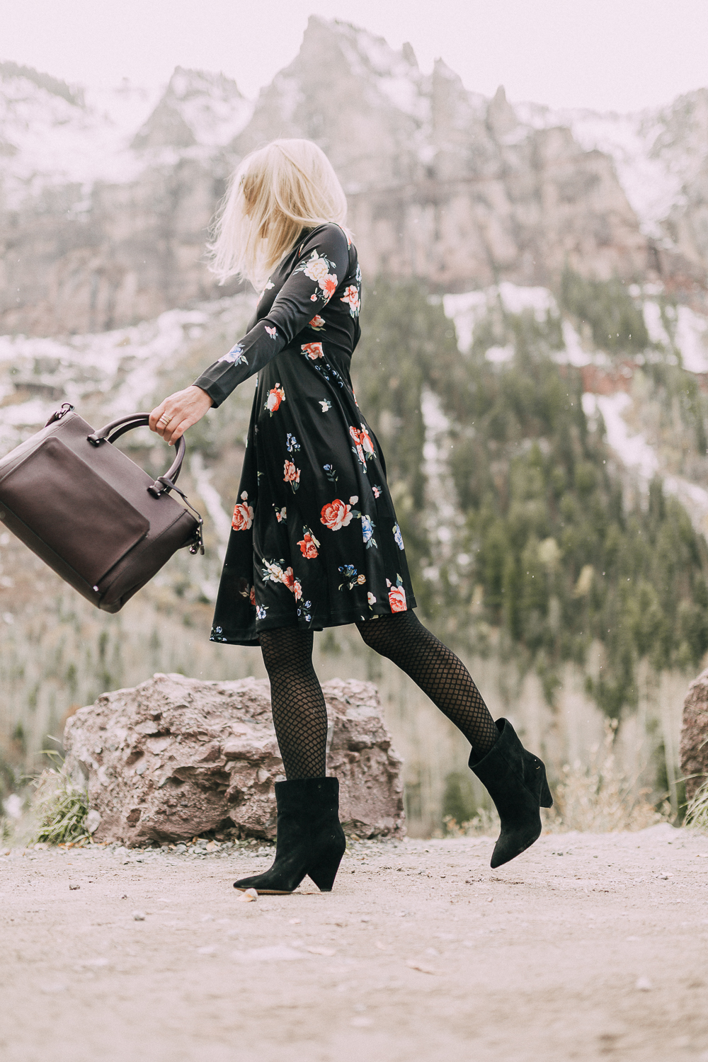 black regina Suede Booties by Vince Camuto paired with black floral print dress and leather burgundy tote bag on blonde woman in rocky mountains