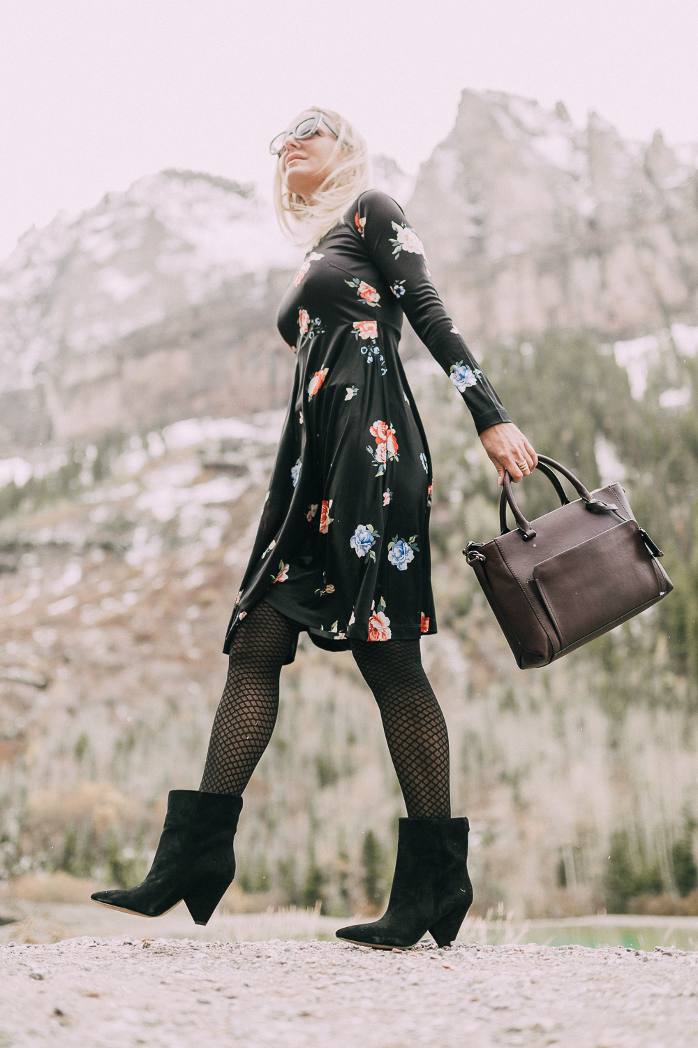 blond woman wearing black vince camuto regina Suede Booties paired with black floral print dress carrying burgundy tote bag with rocky mountains background