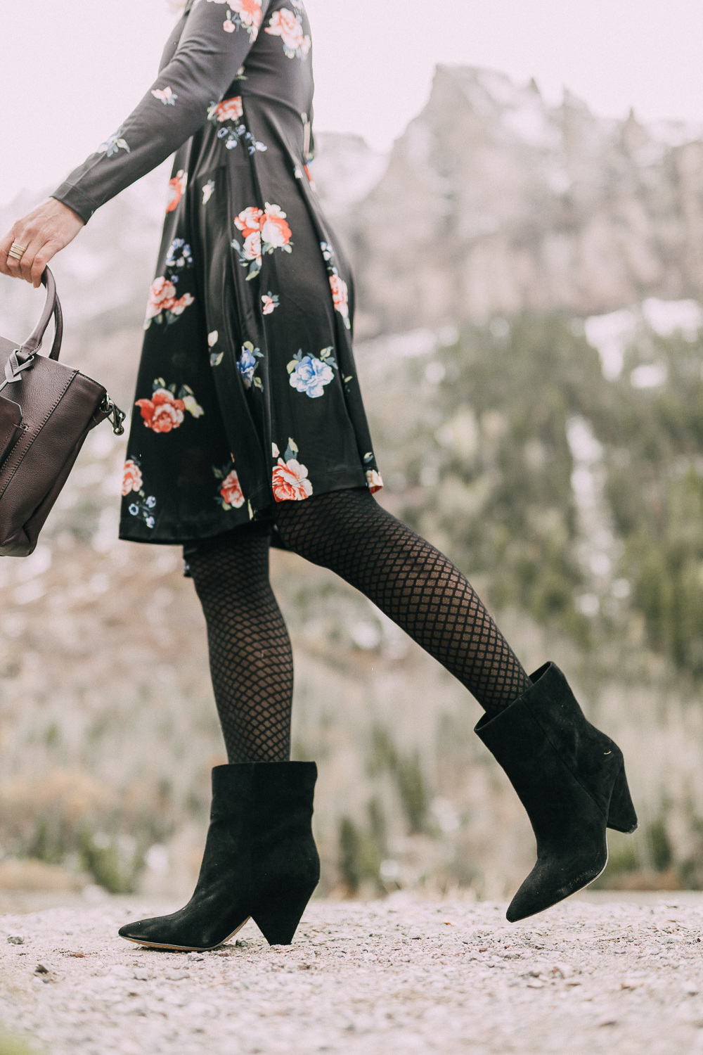 close up shot of regina black suede vince camuto booties on blond woman in rocky mountains usa