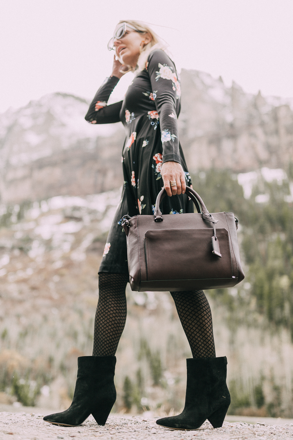 Suede Booties by Vince Camuto paired with black floral print dress and burgundy tote bag on blonde woman in rocky mountains