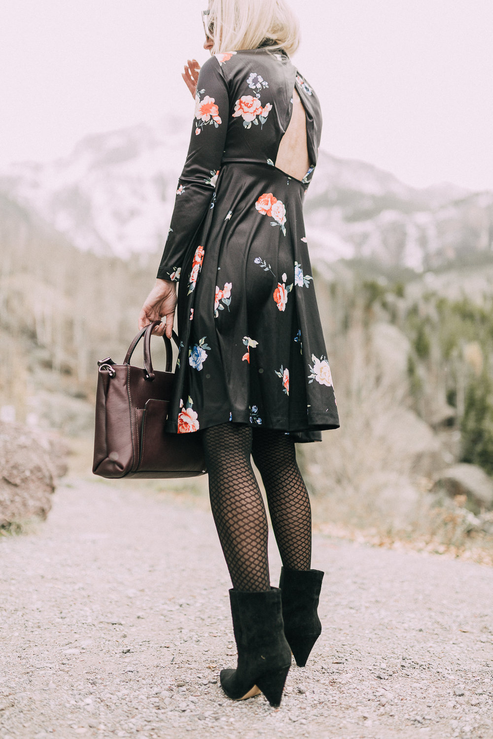 back of woman wearing regina black suede Booties by Vince Camuto paired with black open-back floral print dress and burgundy tote bag