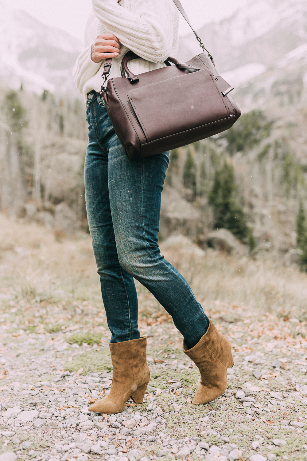 Suede Booties by Vince Camuto paired with white turtleneck cable knit sweater, burgundy tote bag, and white wool coat on blonde woman in the mountains