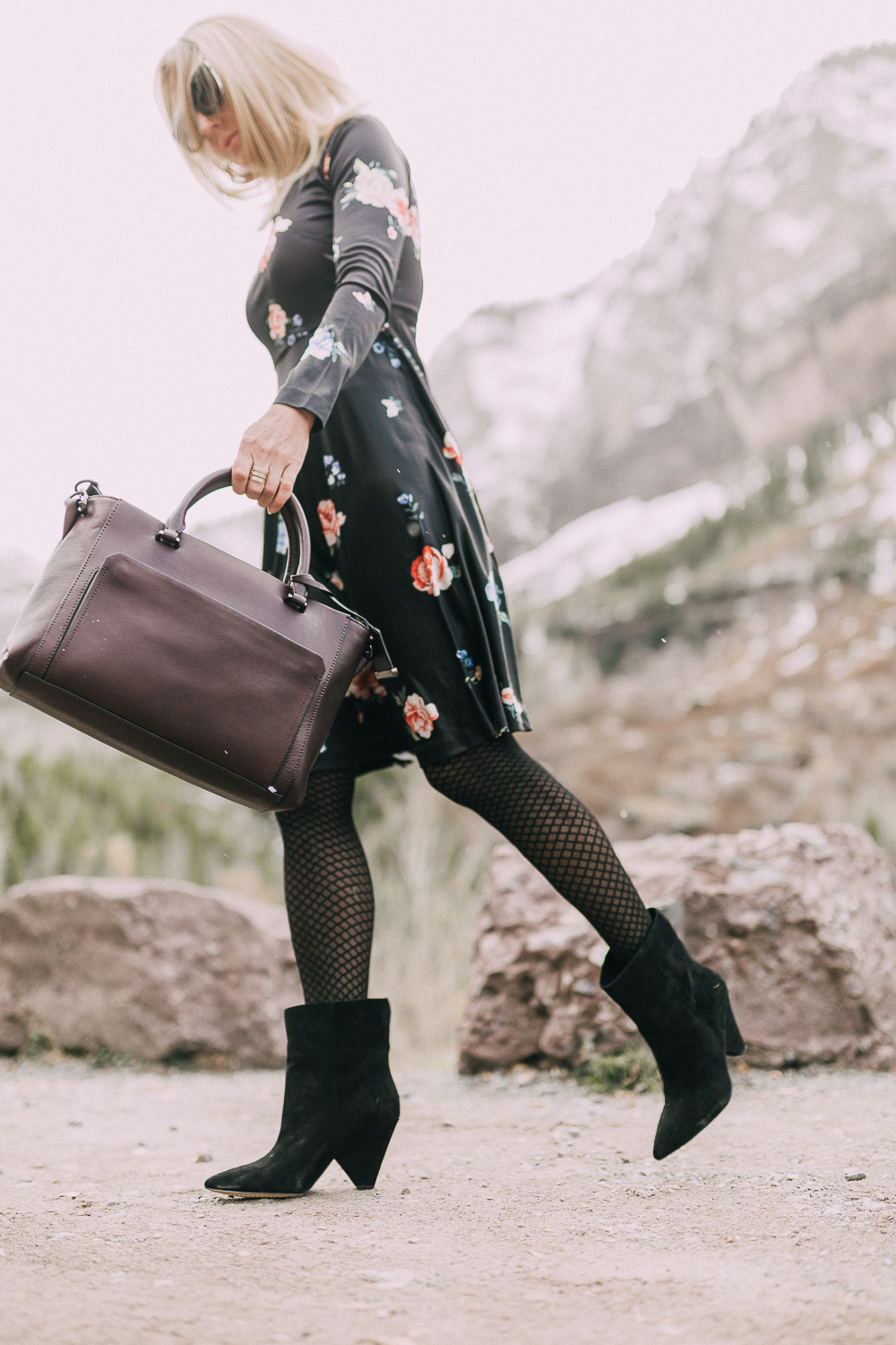 black regina suede Booties by Vince Camuto paired with black floral print dress and burgundy leather tote bag on blonde woman in rocky mountains