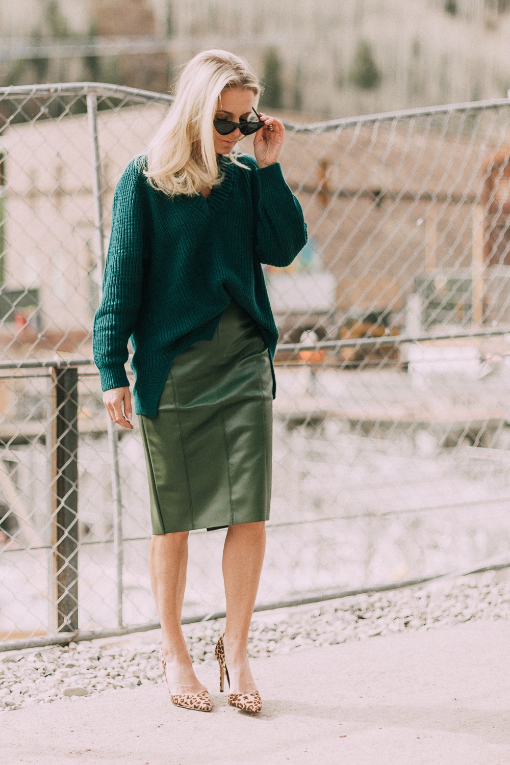 Work Outfit Ideas, what to wear to work, outfit ideas that are modern and unexpected from Express, featuring a faux leather green pencil skirt, and chunky knit tunic sweater in green, and leopard print pumps on blonde woman