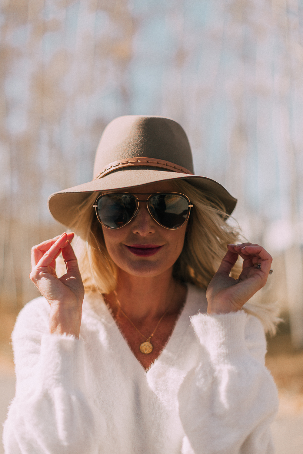 blonde woman wearing rag & bone hat, sunglasses, white sweater, and gold necklace