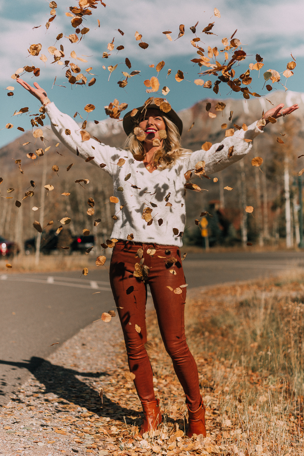 Blonde woman in Telluride, Colorado wearing brown leather pants by Frame with a white fuzzy Halogen sweater, Saint Laurent boots, and a rag & bone hat, throwing leaves in the air