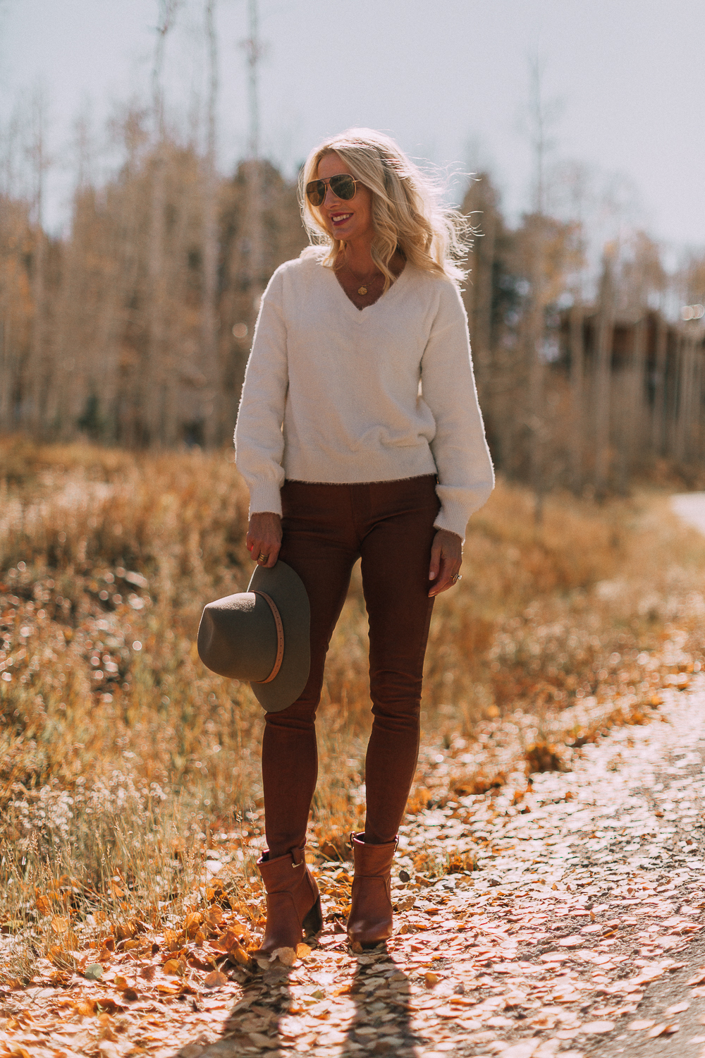 Blonde woman in Telluride, Colorado wearing brown leather pants by Frame with a white fuzzy Halogen sweater, Saint Laurent boots, and a rag & bone hat