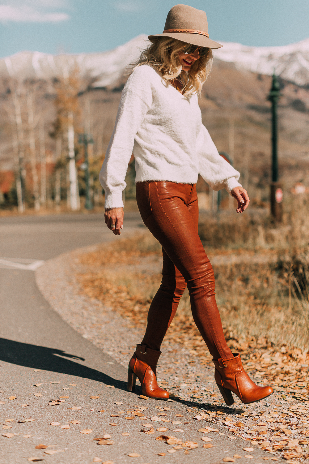 Blonde woman in Telluride, Colorado wearing brown leather pants by Frame with a white fuzzy Halogen sweater, Saint Laurent boots, and a rag & bone hat, sharing how to wear leather pants
