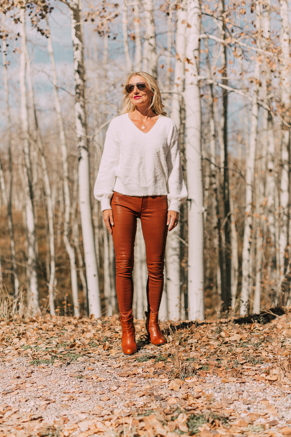 sharing how to wear leather pants in these brown frame leather pants and white fuzzy sweater