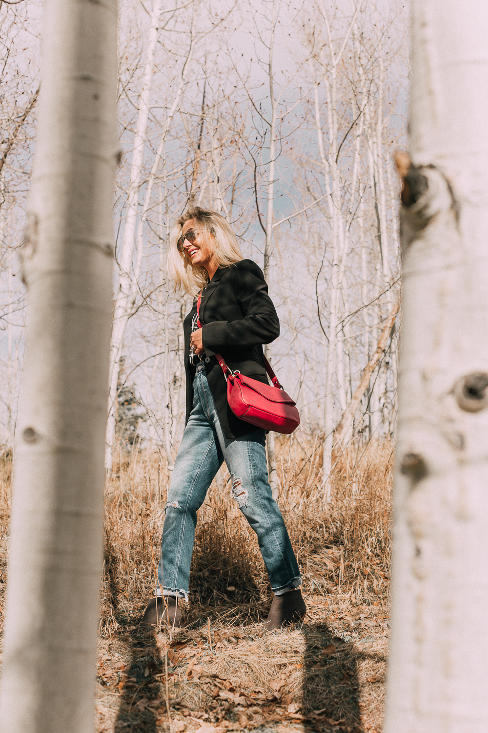Bootie Trend, styling gray suede short ankle boots by Vince Camuto with Mother cropped jeans, rails black and white plaid shirt, black donna karen blazer and a red crossbody bag on fashion blogger Erin Busbee