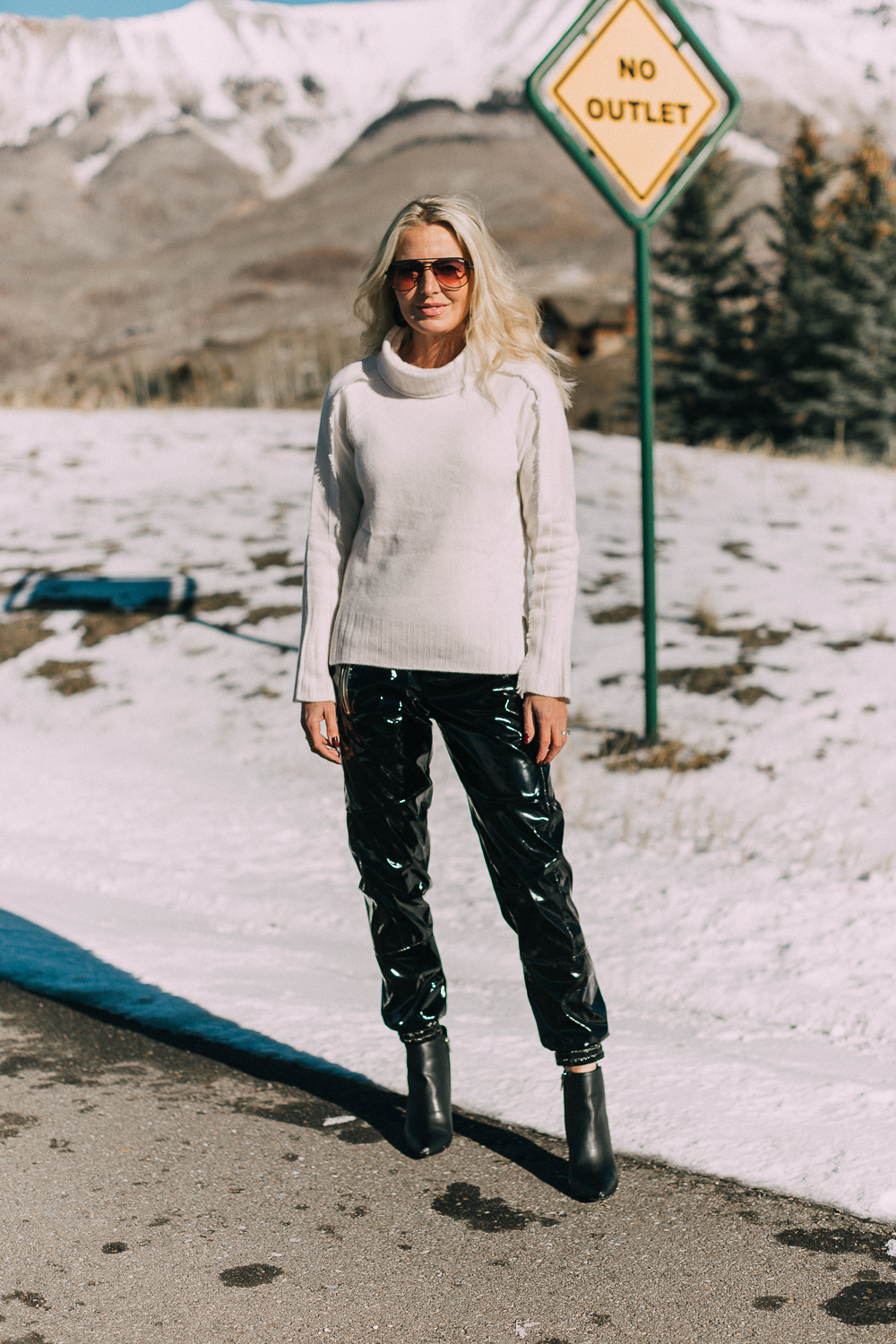 Fashion blogger over 40 Erin Busbee of BusbeeStyle.com wearing black vinyl jogger pants by RtA with black Michael Kors booties and a white cashmere turtleneck sweater by Brochu Walker, in Telluride, Colorado
