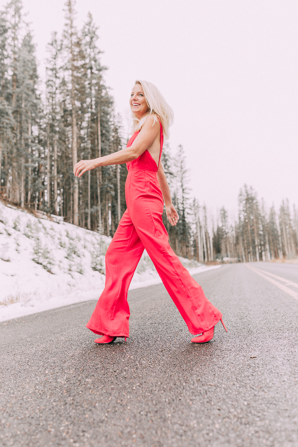 Fashion blogger Erin Busbee of BusbeeStyle.com sharing outfits for New Years Eve including this red jumpsuit by by the way. from Revolve paired with red booties