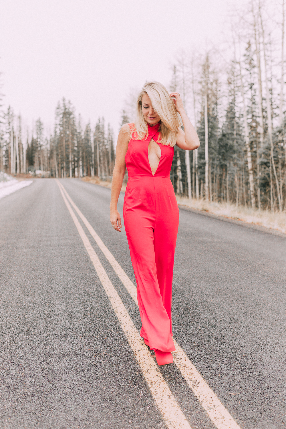 Fashion blogger Erin Busbee of BusbeeStyle.com wearing a red jumpsuit by by the way. from Revolve with red booties in Telluride, Colorado